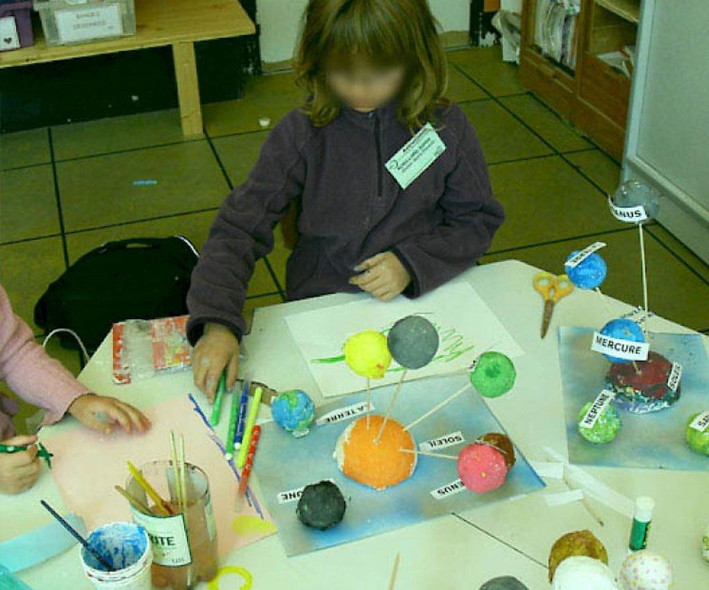 Des enfants en train de créer un système solaire avec des boules de polystyrènes