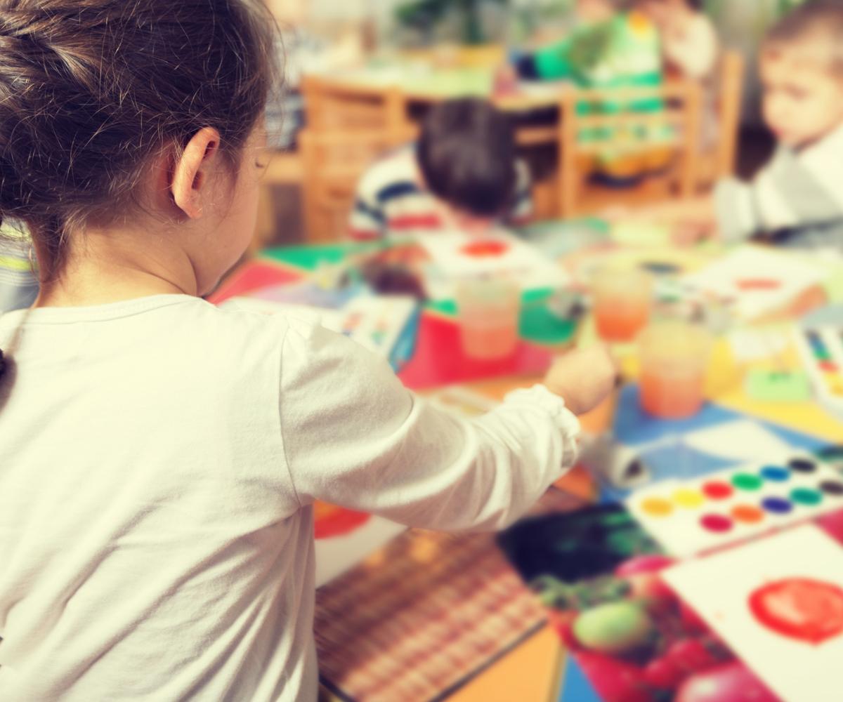 des enfants peignent des dessins autour d'une table.