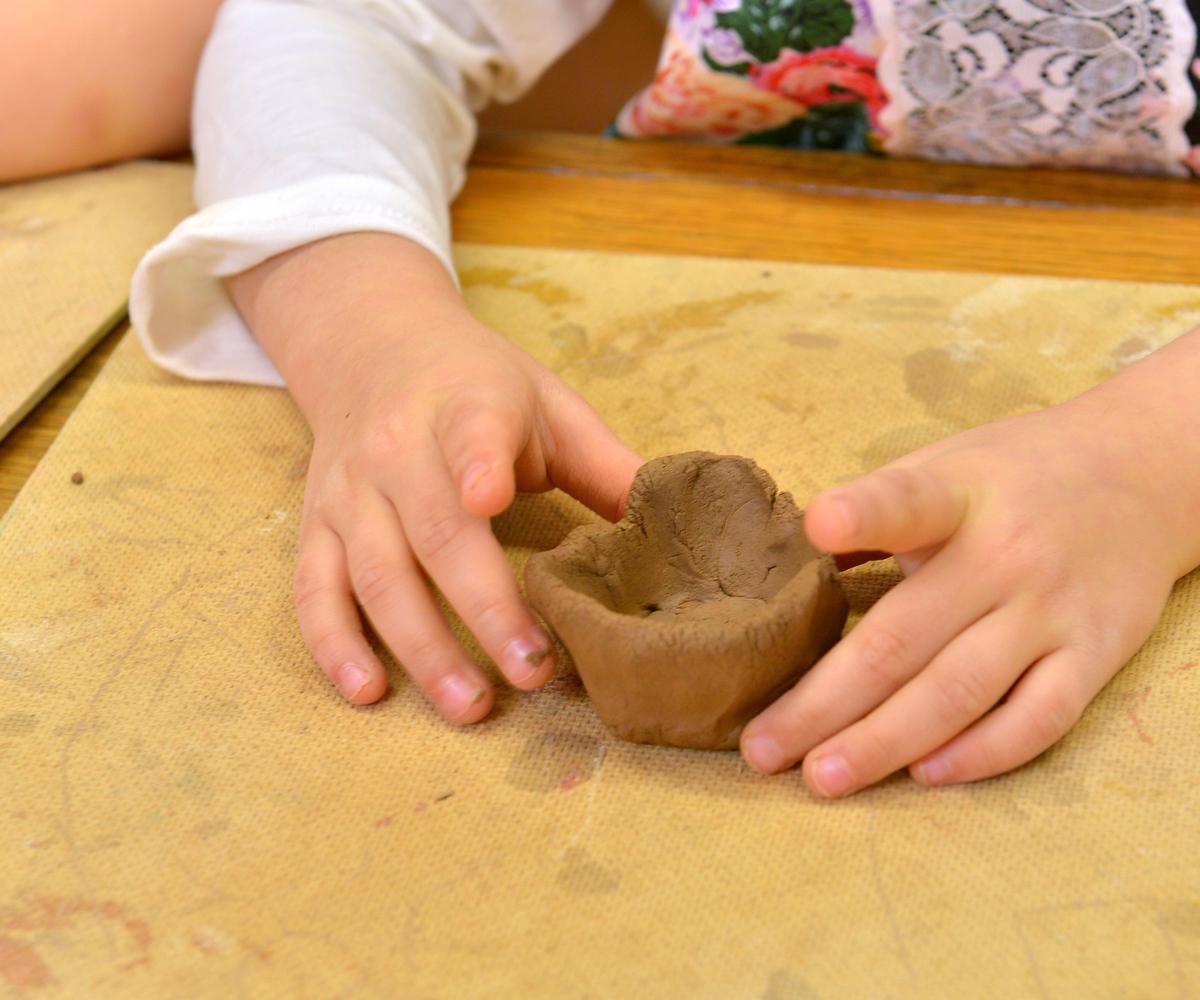Les bras d'une petite fille qui fabrique un pot en argile a