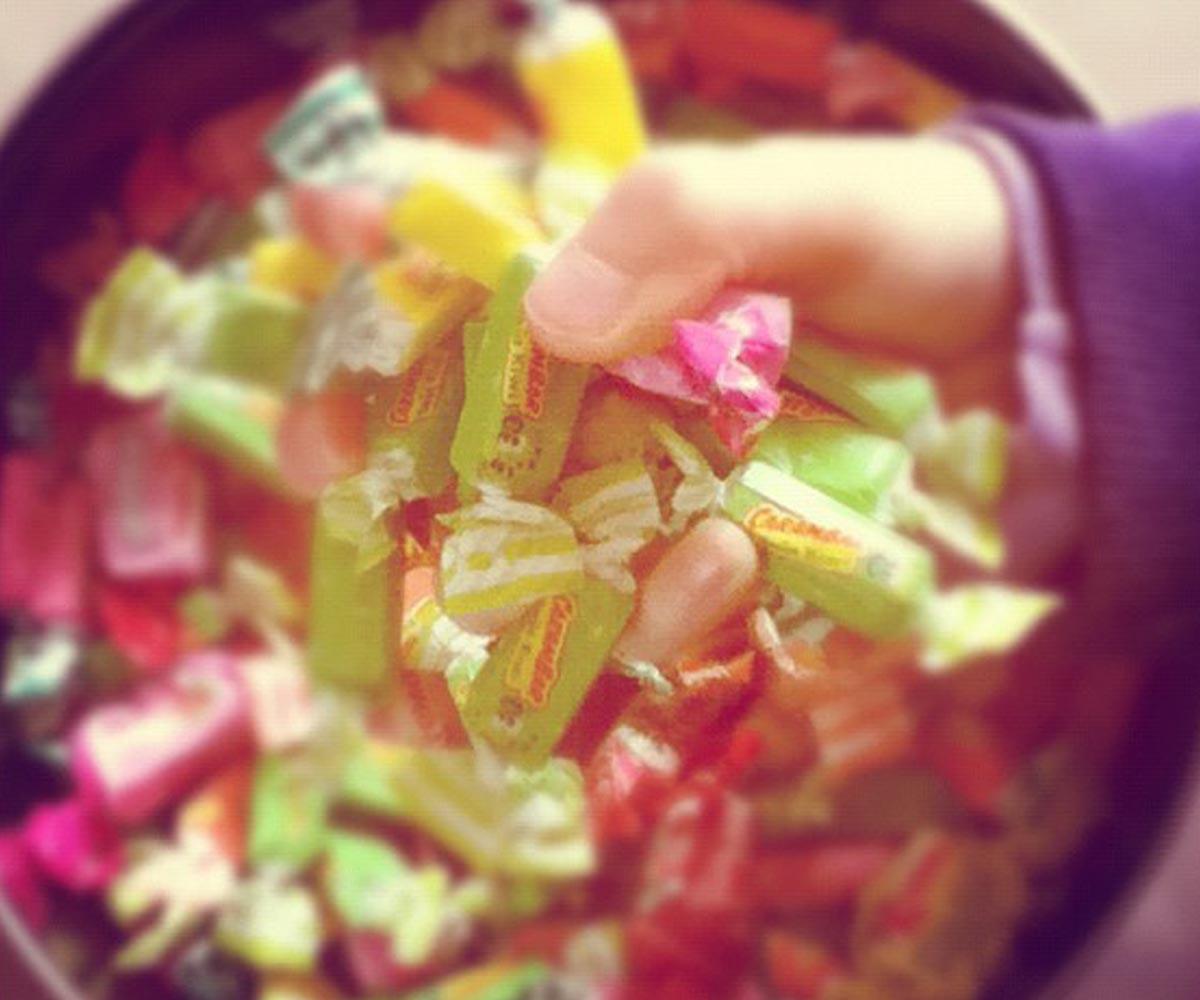 Une poignée de bonbons prise dans un récipient.