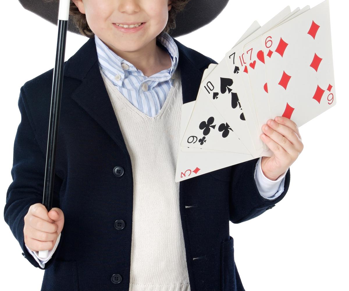 Un garçon déguisé en magicien avec baguette, chapeau haut de forme et cartes de jeu géantes