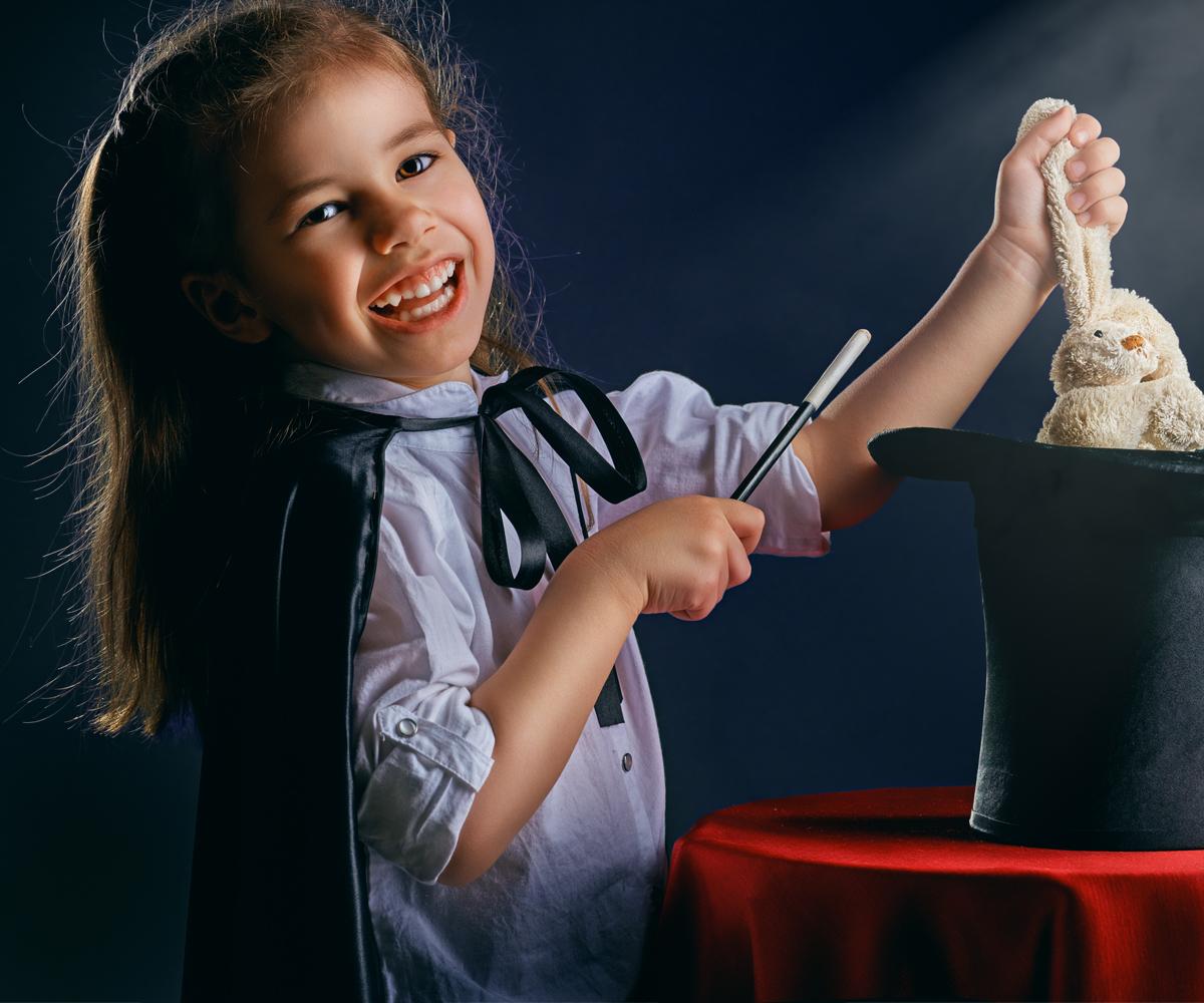 Petite fille sort un lapin peluche de son chapeau de magicienne