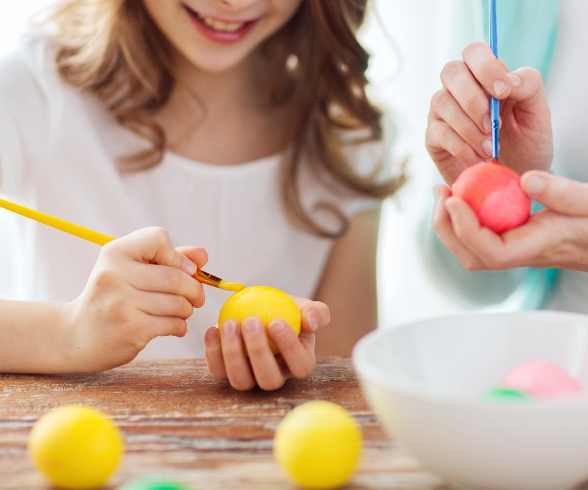 2 jeunes filles décorent des œufs à la peinture jaune et rouge