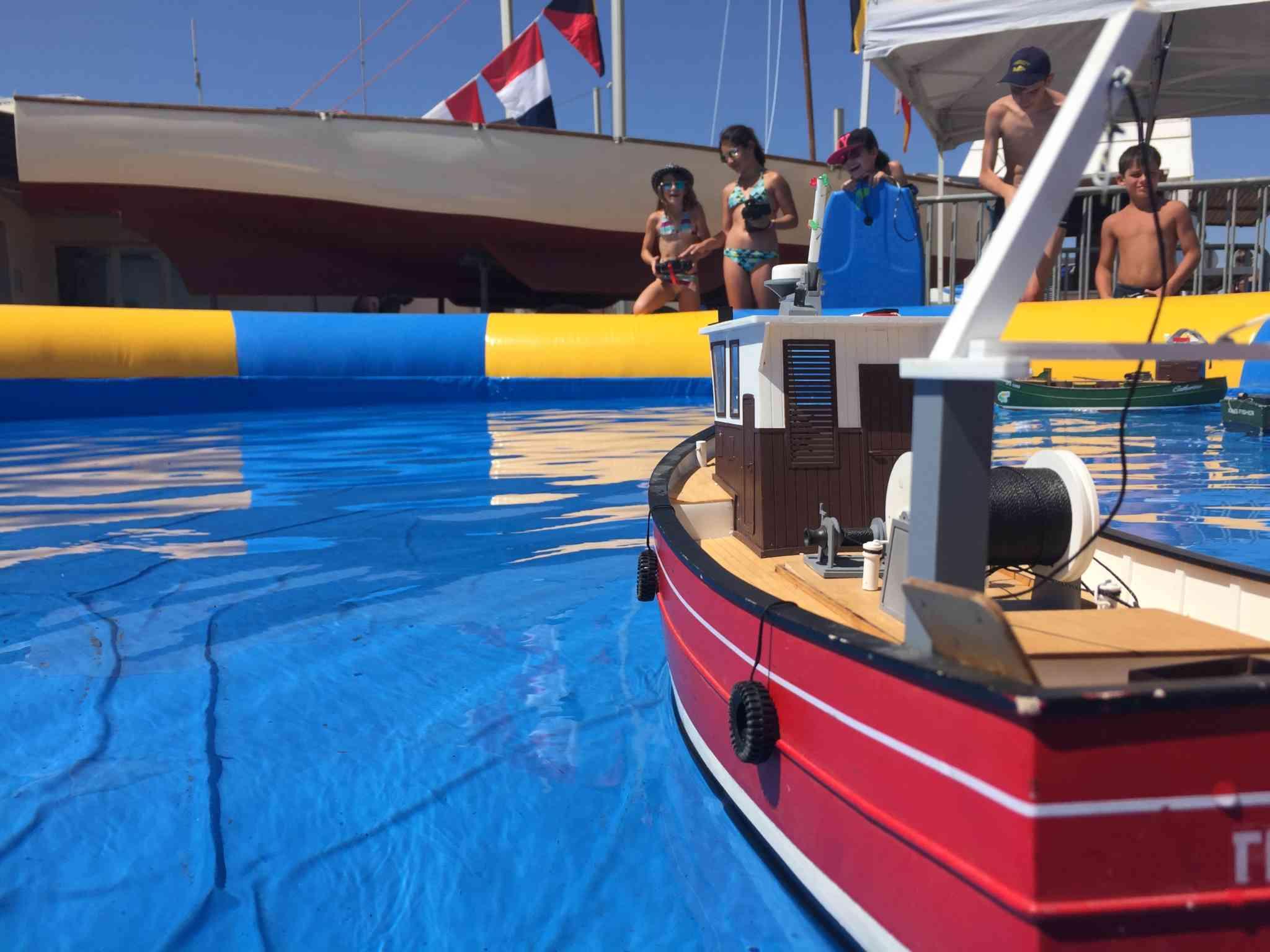 une piscine, un bateau radiocommandé et des enfants autour